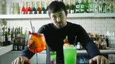 konyak : attractive bartender stands behind bar with colored cocktails decorated fruit and ice, lot of bottles with expensive alcohol in background