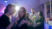 koňak : girlfriends gossip at the bar girl with an alcoholic beverage looks at the screen of mobile phone behind the bar counter on background of lumiere