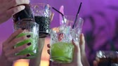 охлажденный : close-up of people hands make toast with glasses with alcoholic multi-colored cocktails at nightclub