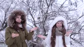 блаженный : snowfall, cheerful girlfriends enjoy snow with hands up outdoors in winter park at weekend