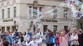 soap bubbles : Wroclaw, Poland 12 May 2018: children have fun, woman makes big bubbles for a crowd of people at street festival in slow motion in Wroclaw, 12 May 2018. Stock Footage