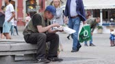 безработные : Wroclaw, Poland 12 May 2018: homeless man with beard eats from plastic plate sitting on the street in Wroclaw, 12 May 2018.