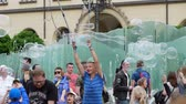 varinha : Wroclaw, Poland 12 May 2018: bubble entertainment, happy people playing with soap bubbles in city on town square in Wroclaw, 12 May 2018. Vídeos