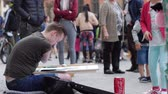 alms : Wroclaw, Poland 12 May 2018: contemporary art, handicapped male creates paintings and generous passers throw money into jar at town square in Wroclaw, 12 May 2018.