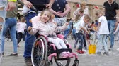 varinha : Wroclaw, Poland 12 May 2018: happy life of children with disabilities, little girl in wheelchair is rejoices with soap bubbles on open air in Wroclaw, 12 May 2018.