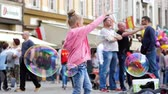 varinha : Wroclaw, Poland 12 May 2018: little girl with soap bubbles spending time on pedestrian street in city in Wroclaw, 12 May 2018.