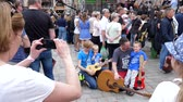 instrumentalist : Wroclaw, Poland 12 May 2018: tourist event, people take photos on cell phone family of guitarists but city square in Wroclaw, 12 May 2018. Stock Footage