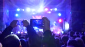instrumentalist : crowd of youth with gadget in hands at rock concert in floodlight lighting at night Stock Footage