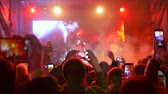 instrumentalist : leisure of modern youth, mobile phones in hands spectators shoot video of rock concert on brightly lit stage at vacation Stock Footage
