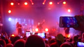 instrumentalist : rock festival, many people with gadget in hands make video recording at concert in floodlight lighting
