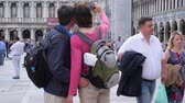 marco : Venice, Italy 19 May 2018: tourists with backpacks are photographed on mobile phone at St. Marks Square in Venice, 19 May 2018. Stock Footage