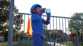 ustalık : Rollerblading kid drinks pure water from bottle on open air in backlight close-up Stok Video
