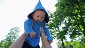 başlık : child life, happy cute infant in blue hood plays in air in vivid sunlight close-up