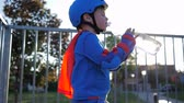 thirst quenching : drinking water, Rollerblading child in helmet with plastic bottle into hand outdoors in backlight Stock Footage