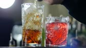 coquetel : person pour out alcohol in glass with ice and near is bright ready cocktail close-up Stock Footage