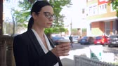 nervous : unnerved business lady in eyeglasses drinking coffee on the street and thinking about something Stock Footage