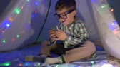 kids tent : smiling child looks into a gadget sitting in a wigwam decorated with garland at home