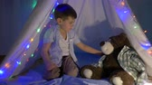 kids tent : small boy playing with teddy bear hiding in wigwam decorated with garland at home in evening