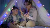 kids tent : mother tells a fairy tale and plays with sons in wigwam with a decor garland in the evening Stock Footage