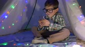 kids tent : modern childhood, happy kid looks into smartphone sitting in a wigwam decor with a garland at home Stock Footage