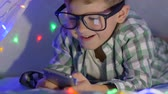 kids tent : smart kid in glasses watches video on mobile phone in wigwam with garland at home close-up