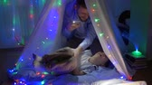 kids tent : tickles, child with the parent hid in the tent, daddy has fun with toddler in children room with vivid lights at night in vacation at home