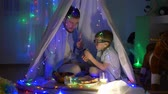 kids tent : men secrets, small boy with daddy gossips while eating sitting in tent with bright lights at children room in evening
