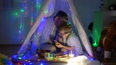 kids tent : male gossip, Dad tells child secrets during dinner after dinner in teepee with festoon indoors in evening