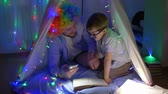 kids tent : little boy is having fun with clown and reading fairy tales sitting in tent decorated with bright garland at night indoors