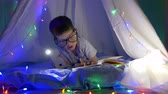 kids tent : intelligent toddler into eyeglasses reading book in flashlight lighting lying in tent with bright lights at children room