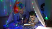 kids tent : home time, happy child with dad into funny wig reading book in light of flashlight lying at magical tent with garlands in evening indoors