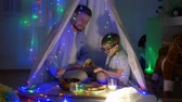 kids tent : happy childhood, daddy with son eating buns sitting in tent decorated with garlands at night indoors in evening