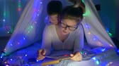 kids tent : family atmosphere bedtime story, caring mother reads fairy tales to kid lying in teepee with garlands at children room