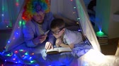 kids tent : children fairy tales, bearded men into clown wig with son read book into lighting of flashlight in tent with garlands indoors in evening