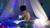 kids tent : book reading, clever kid into spectacles reading fairy tales in flashlight lighting lying into tent with garlands at home in evening