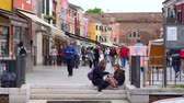 Венеция : Burano, Italy 19 May 2018: girls eating junk food on street sitting on the steps on background of colorful houses and tourists in Burano, 19 May 2018. Стоковые видеозаписи