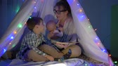 conta : happy family, mom reads fairy tales to her sons sitting in the wigwam in the evening
