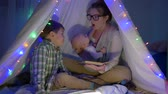 kids tent : family leisure, mother reads an interesting book to her two sons sitting in the wigwam in the evening Stock Footage