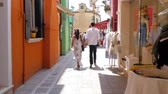 типичный : Burano, Italy 19 May 2018: tourists at europe, couple in love walking holding hands along colored shop windows on street in Burano, 19 May 2018.