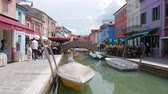 типичный : Burano, Italy 19 May 2018: people going to village street along water canal with motor vessel and color architecture in Burano, 19 May 2018. Стоковые видеозаписи
