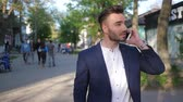 время приема пищи : Kherson, Ukraine 22 April 2018: handsome guy talking on cell phone while walking down city street in Kherson, 22 April 2018.