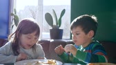 panqueca : childrens breakfast in cafe, Adorable little boy with girlfriend eating pancakes indoors with natural light Vídeos