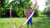 urlop : happy childhood, cute kid is played with pink ribbon on green glade in nature Wideo
