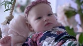 maličký : child peace, lovely baby with fashionable wreath on head resting on swing in room close-up Dostupné videozáznamy