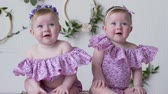 white headband : female twins in pink clothes posing on photo shoot on background of wall with decor closeup Stock Footage