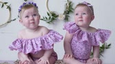white headband : twins in pink clothes posing on photoshoot on background of wall with decor closeup Stock Footage