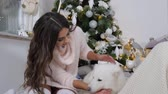 ziyafet : girl brunette in long sweater have fun with white pet on floor under green fir tree