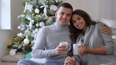 bright room : husband and wife holding large white cups in their hands on his home couch in the morning on background of decorated xmas tree