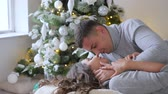 bright room : loving emotions, husband with admiration looks at his wife and gently kisses her against the background of decorated xmas tree Stock Footage