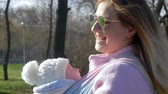 sling : parental love, joyful mother cares for baby in arms outdoors in spring on weekends close-up Stock Footage